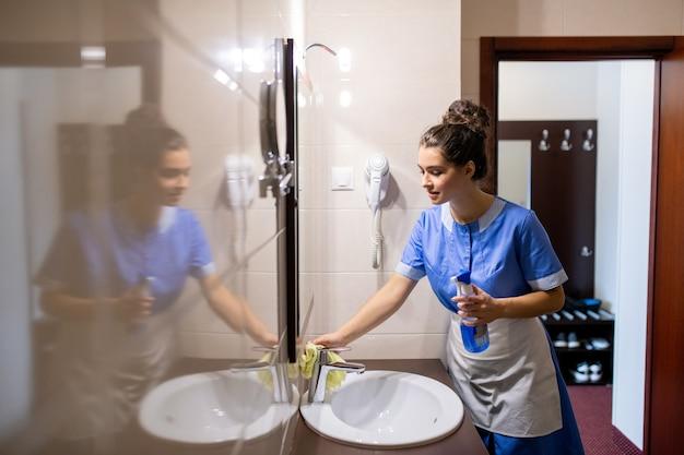 Jovem empregada de quarto contemporânea com pia para limpeza de detergente no banheiro enquanto fica em frente ao espelho