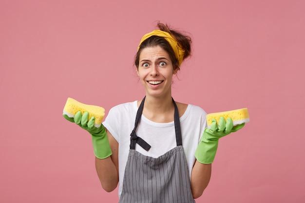 Jovem empregada doméstica usando avental e luvas de borracha segurando duas esponjas limpas nas mãos, olhando com expressão de surpresa, sorrindo amplamente mostrando seus dentes brancos perfeitos. limpeza de primavera