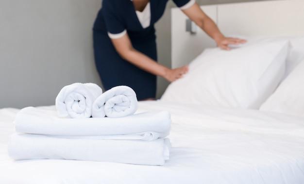 Jovem empregada fazendo cama em um quarto