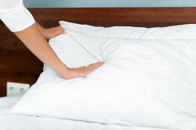 Jovem empregada fazendo cama no quarto de hotel