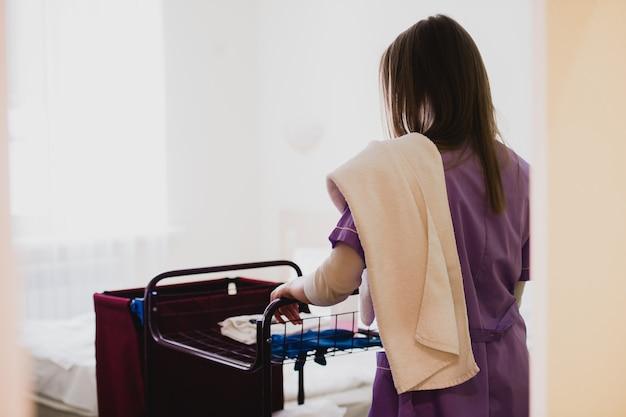 Jovem empregada feminina empurrando o carrinho durante a limpeza de quartos de hotel