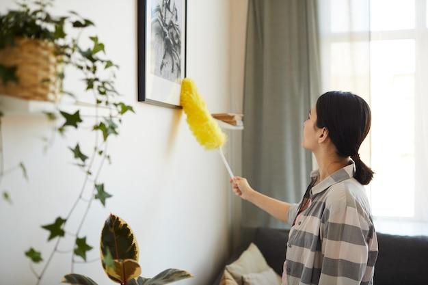 Jovem empregada limpando a poeira com o pincel da foto na sala de estar de casa