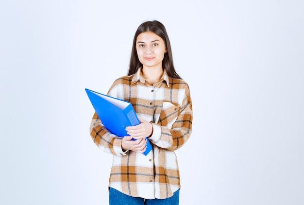 Jovem empregada segurando o suporte azul na parede branca.