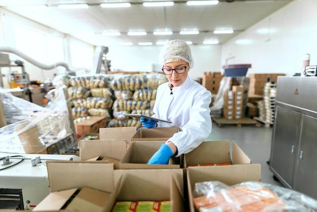 Jovem empregado caucasiano em uniforme estéril usando tablet para logística. interior da fábrica de alimentos.