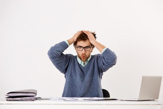 Jovem empregado masculino, tenso e pressionado, trabalhador de escritório ou empresário perturbado, expirando ao olhar para documentos e relatórios, não pode lidar com a pressão dos prazos