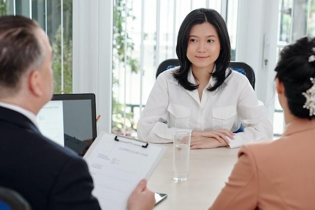 Jovem empresária adorável e sorridente respondendo a perguntas do gerente de recursos humanos e do ceo da empresa