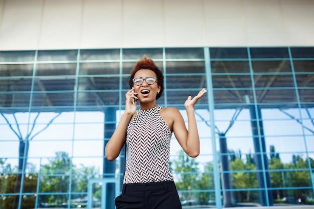 Jovem empresária africana bem sucedida, falando no telefone, sobre o centro de negócios.