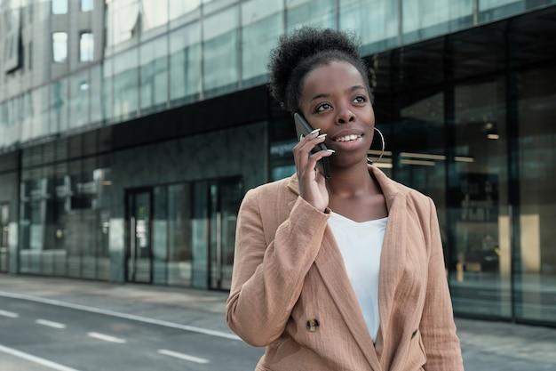 Jovem empresária africana conversa no celular enquanto caminha pela rua da cidade