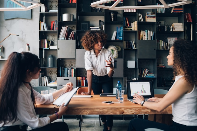 Jovem empresária africana interagindo com colegas no escritório de co-trabalho e trabalhando no projeto