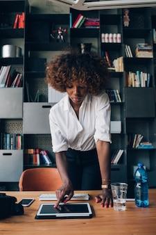 Jovem empresária africana trabalhando com tablet no escritório de trabalho