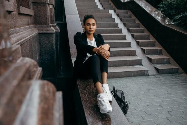 Jovem empresária afro-americana elegante casaco jaqueta sentado nas escadas da cidade e segure um saco.