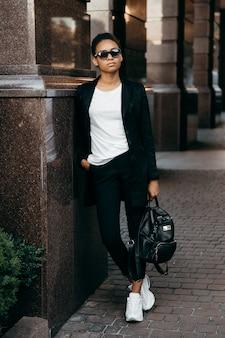 Jovem empresária afro-americana elegante na jaqueta fica na cidade e segura uma sacola.