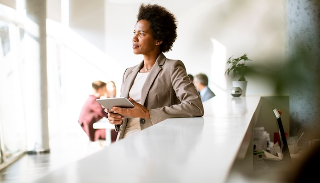 Jovem empresária afro-americana em pé e usando tablet digital em um escritório moderno