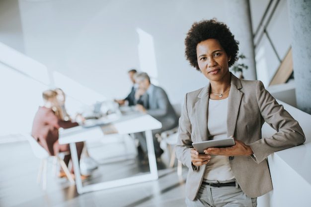 Jovem empresária afro-americana em pé usando tablet digital em um escritório moderno