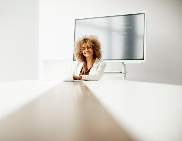 Jovem empresária afro-americana sentada e trabalhando em um laptop em um escritório moderno