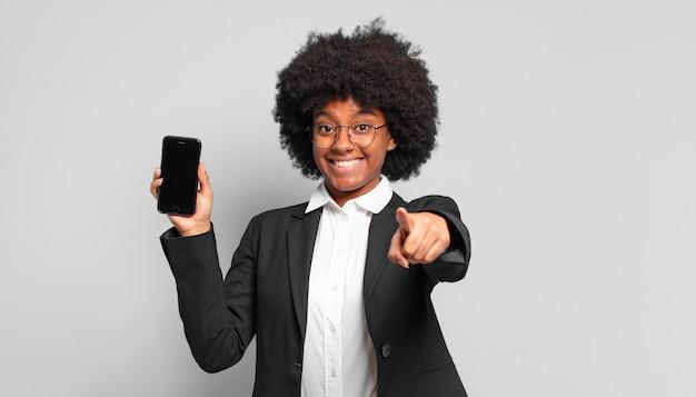 Jovem empresária afro apontando para a câmera com um sorriso satisfeito, confiante e amigável, escolhendo você