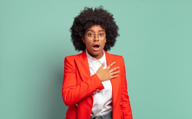 Jovem empresária afro contra parede verde