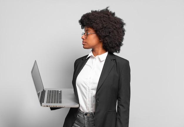 Jovem empresária afro em vista de perfil olhando para copiar o espaço à frente