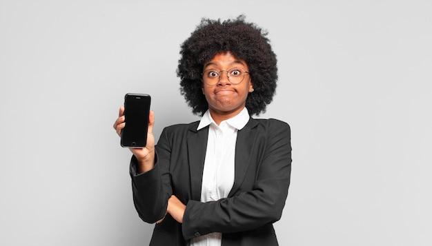 Jovem empresária afro encolhendo os ombros, sentindo-se confusa e incerta, duvidando com os braços cruzados e olhar perplexo. conceito de negócios