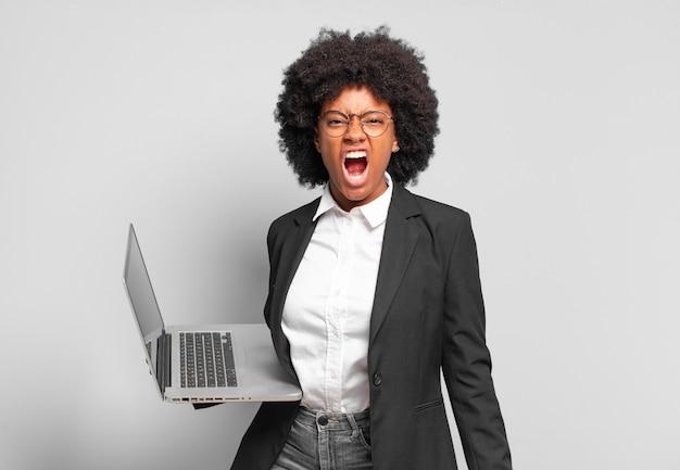 Jovem empresária afro gritando agressivamente, parecendo muito zangada, frustrada, indignada ou irritada, gritando que não. o negócio
