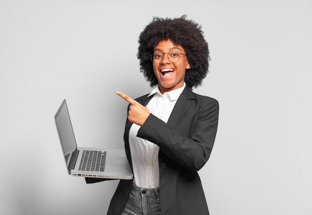 Jovem empresária afro olhando animada e surpresa, apontando para o lado e para cima para copiar o espaço. conceito de negócios