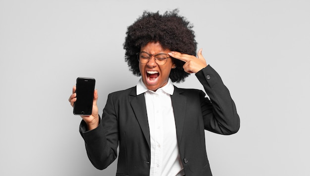 Jovem empresária afro olhando infeliz e estressada, gesto de suicídio fazendo sinal de arma com a mão, apontando para a cabeça.