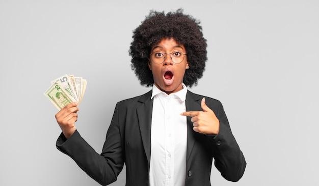 Jovem empresária afro parecendo chocada e surpresa com a boca aberta, apontando para si mesma. conceito de negócios