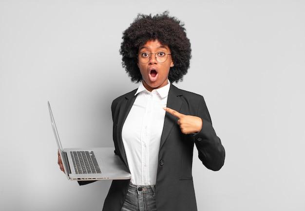 Jovem empresária afro parecendo chocada e surpresa com a boca escancarada, apontando para si mesma