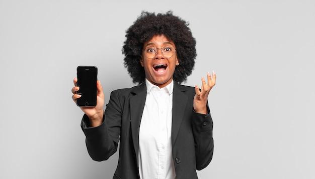 Jovem empresária afro parecendo desesperada e frustrada, estressada, infeliz e irritada, gritando e gritando. conceito de negócios