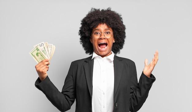 Jovem empresária afro parecendo desesperada e frustrada, estressada, infeliz e irritada, gritando e gritando.