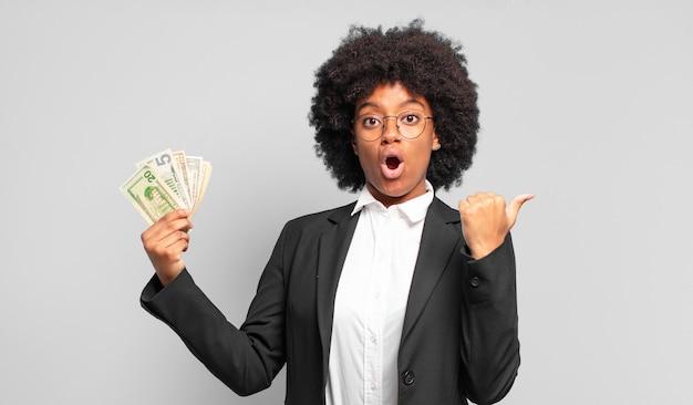 Jovem empresária afro parecendo espantada com a descrença, apontando para o objeto ao lado e dizendo uau, inacreditável. conceito de negócios