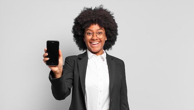 Jovem empresária afro parecendo feliz e agradavelmente surpresa, animada com uma expressão de fascínio e choque.