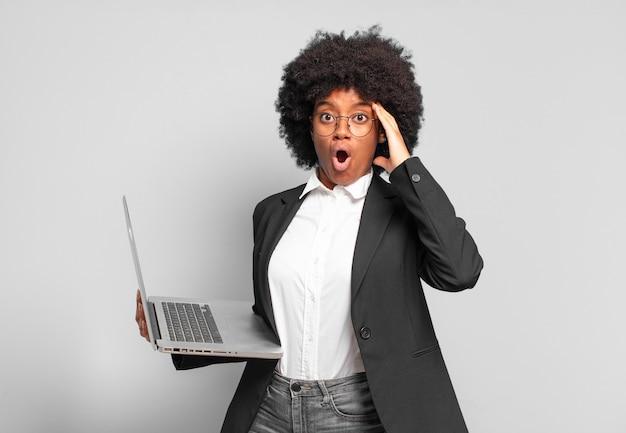 Jovem empresária afro parecendo feliz, espantada e surpresa, sorrindo e percebendo uma boa notícia incrível. conceito de negócios