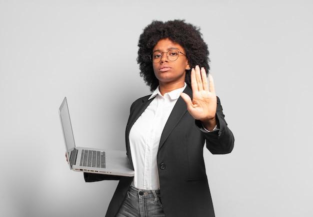 Jovem empresária afro parecendo séria, severa, descontente e irritada mostrando a palma da mão aberta fazendo gesto de pare