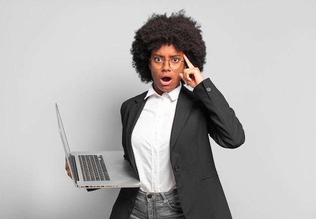 Jovem empresária afro parecendo surpresa, boquiaberta, chocada, percebendo um novo pensamento, ideia ou conceito. conceito de negócios