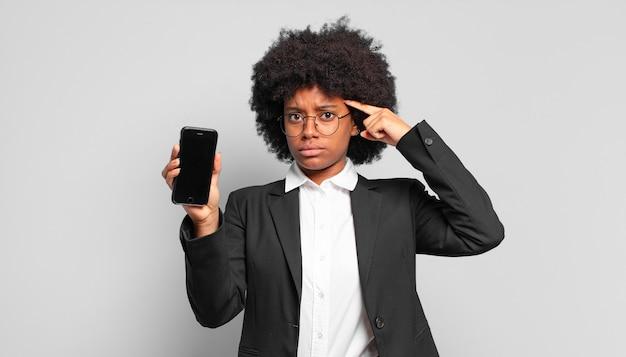 Jovem empresária afro se sentindo confusa e perplexa, mostrando que você é louco, louco ou maluco. conceito de negócios