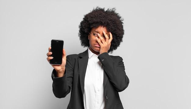 Jovem empresária afro se sentindo entediada, frustrada e com sono depois de uma tarefa cansativa, maçante e tediosa, segurando o rosto com a mão. conceito de negócios