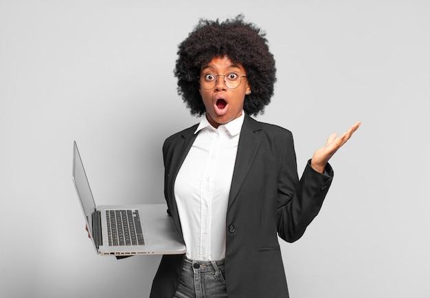 Jovem empresária afro se sentindo extremamente chocada e surpresa, ansiosa e em pânico, com um olhar estressado e horrorizado. conceito de negócios