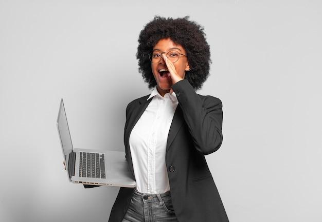 Jovem empresária afro se sentindo feliz, animada e positiva, dando um grande grito com as mãos perto da boca, gritando. conceito de negócios