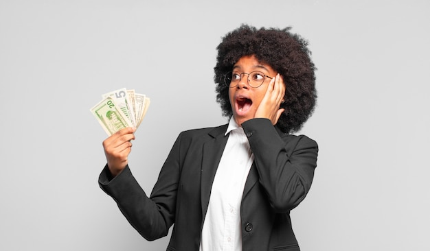 Jovem empresária afro se sentindo feliz, animada e surpresa, olhando para o lado com as duas mãos no rosto. conceito de negócios