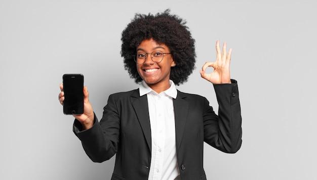 Jovem empresária afro se sentindo feliz, relaxada e satisfeita, mostrando aprovação com um gesto ok, sorrindo. conceito de negócios