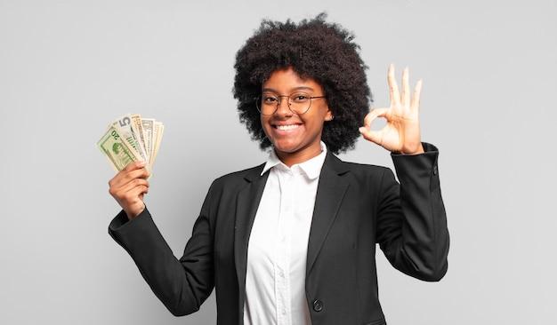 Jovem empresária afro se sentindo feliz, relaxada e satisfeita, mostrando aprovação com um gesto ok, sorrindo.