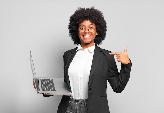 Jovem empresária afro se sentindo feliz, surpresa e orgulhosa, apontando para si mesma com um olhar animado e surpreso