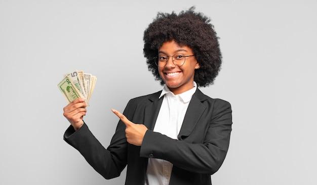 Jovem empresária afro sorrindo alegremente, sentindo-se feliz e apontando para os lados e para cima, mostrando o objeto no espaço da cópia