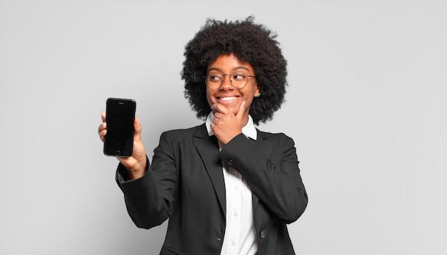 Jovem empresária afro sorrindo com uma expressão feliz e confiante com a mão no queixo, pensando e olhando para o lado.