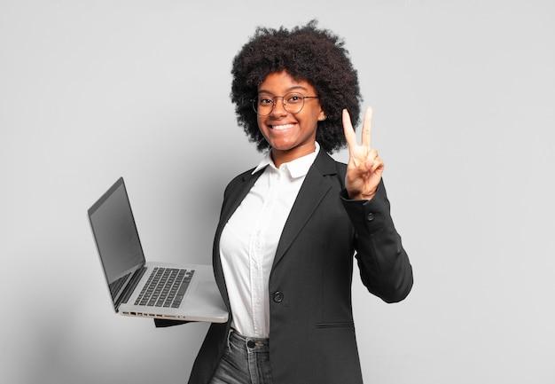 Jovem empresária afro sorrindo e parecendo amigável, mostrando o número dois ou o segundo com a mão para a frente, em contagem regressiva.