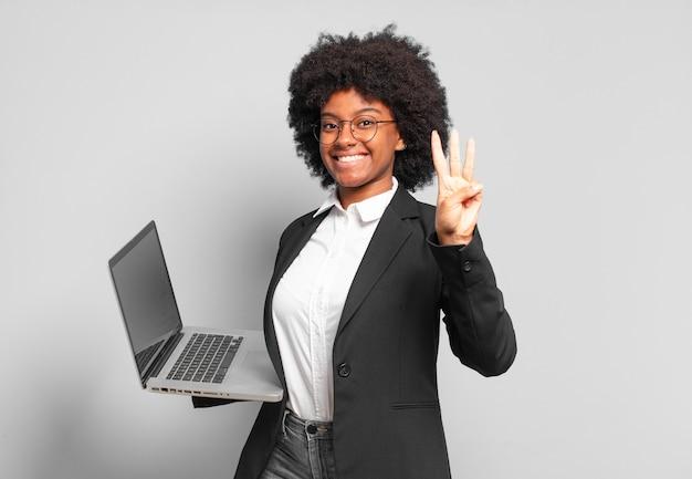 Jovem empresária afro sorrindo e parecendo amigável, mostrando o número três ou terceiro com a mão para a frente, em contagem regressiva. conceito de negócios
