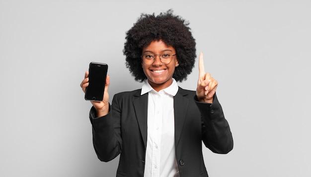 Jovem empresária afro sorrindo e parecendo amigável, mostrando o número um ou primeiro com a mão para a frente, em contagem regressiva. conceito de negócios Foto Premium