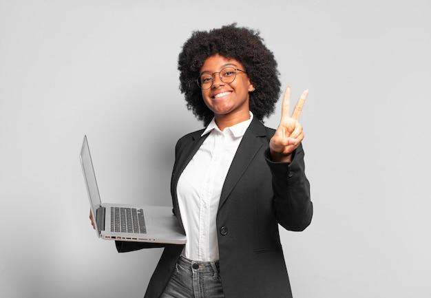 Jovem empresária afro sorrindo e parecendo feliz, despreocupada e positiva, gesticulando vitória ou paz com uma mão. conceito de negócios