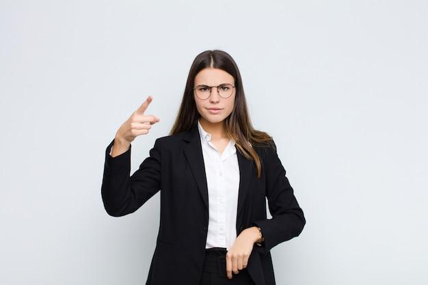 Jovem empresária apontando com uma expressão agressiva com raiva, parecendo um chefe furioso e louco contra a parede branca